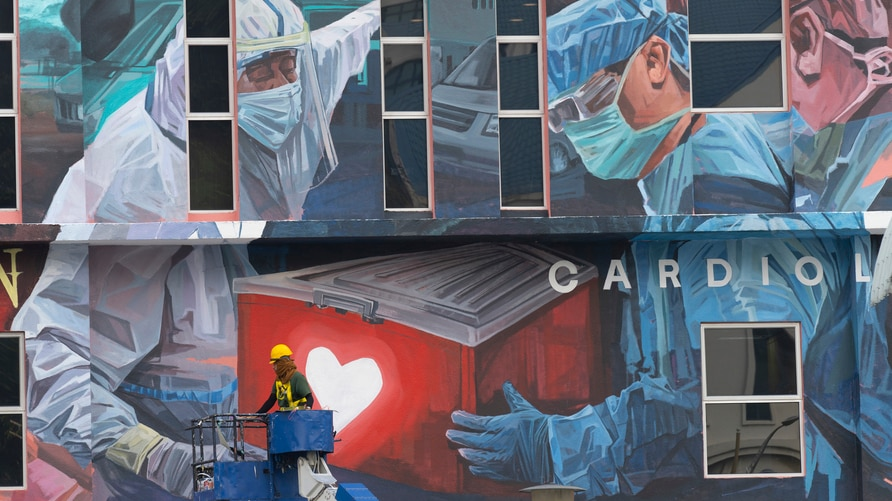 A worker adds finishing touches to giant mural tribute to frontline workers in the COVID-19 coronavirus pandemic outside a…