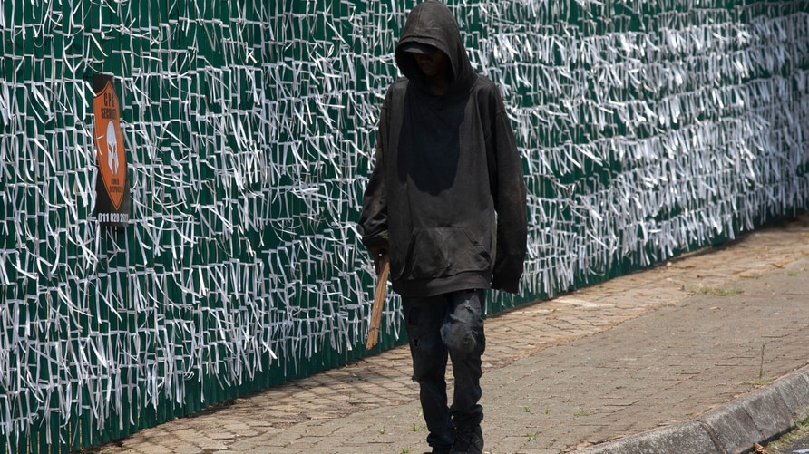 A pedestrian passes the perimeter fence of the Presbyterian Church in Bedfordview, Johannesburg South Africa, Wednesday, Jan…