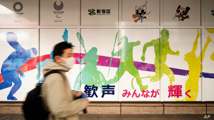 A man wearing a face mask visits the Shinjuku City Hall promoting the Tokyo 2020 Olympics, rescheduled for this summer, in…