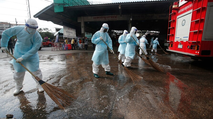 Workers clean the road outside shrimp market in Samut Sakhon, South of Bangkok, Thailand, Monday, Jan. 25, 2021. Thailand on…