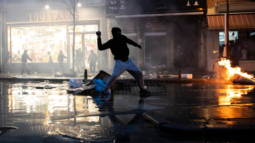Rioters throw stones toward a police office in the Belgium capital, Brussels, Wednesday, Jan. 13, 2021, at the end of a protest…