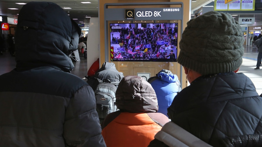 People watch a TV screen showing the news on a violent mob that loyal to U.S. President Donald Trump stormed the U.S. Capitol,…