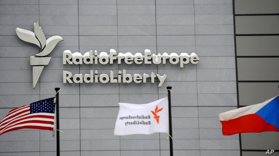 The headquarters of Radio Free Europe/Radio Liberty (RFE/RL) seen with the United States,  RFE/RL and the Czech Republic flags…