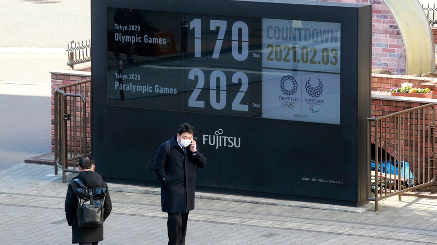 A man stands in front of a countdown clock for Tokyo Olympic and Paralympic Games in Tokyo, Wednesday, Feb. 3, 2021. Pressure…