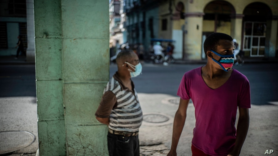 People wearing masks due to the new coronavirus pandemic stand near an area that was gated off to help contain the spread of…