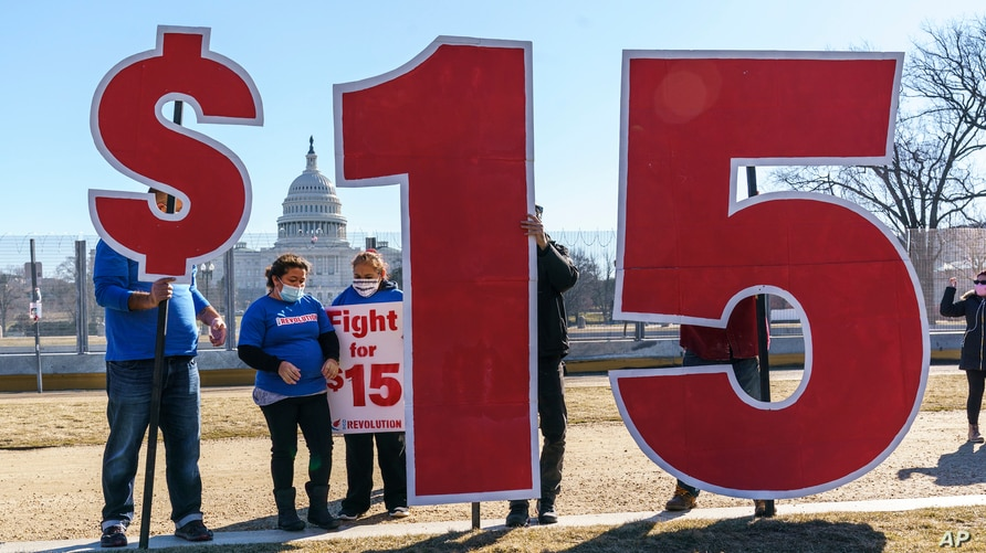 Activists appeal for a $15 minimum wage near the Capitol in Washington, Thursday, Feb. 25, 2021. The $1.9 trillion COVID-19…