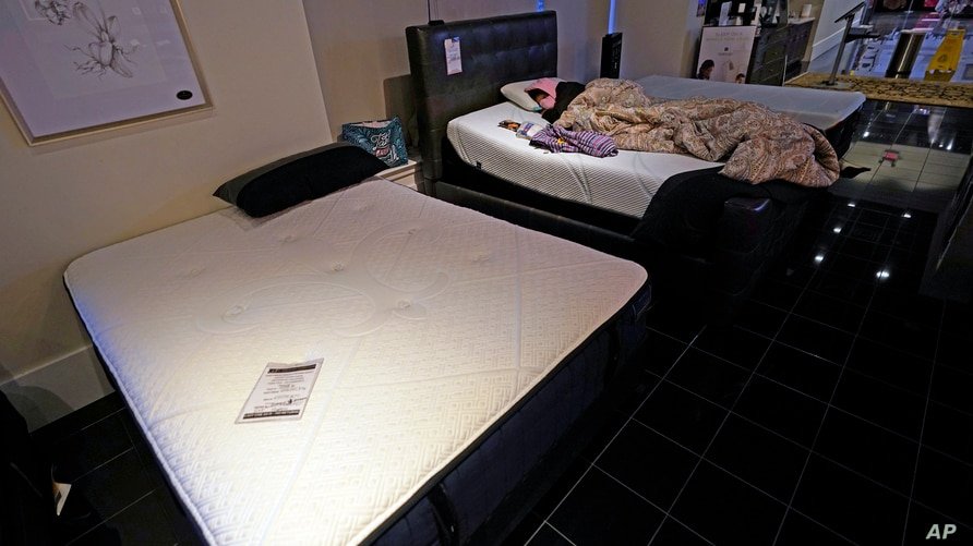 Dialina Gonzalez sleeps on a mattress inside a Gallery Furniture store which opened as a shelter Wednesday, Feb. 17, 2021, in…