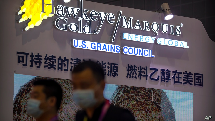 Visitors wearing face masks to protect against the coronavirus look walk past a display from the U.S. Grains Council at the…