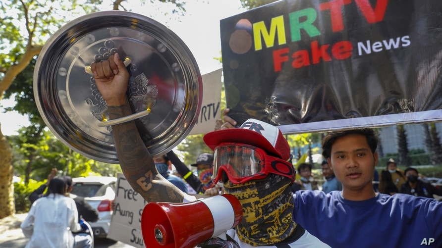 Demonstrators display placards denouncing state and military run TV stations during a protest march against the military coup…