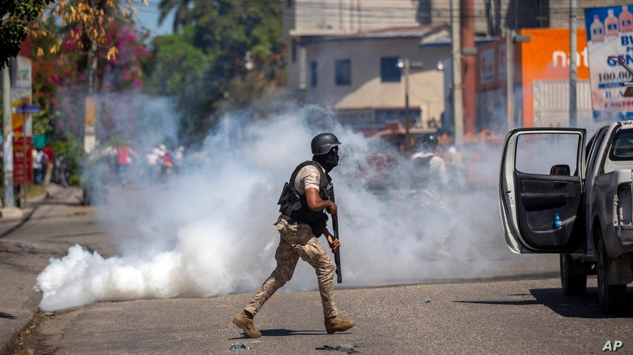 A police officer runs away from tear gas during a protest to demand the resignation of Haiti's president Jovenel Moise in Port…