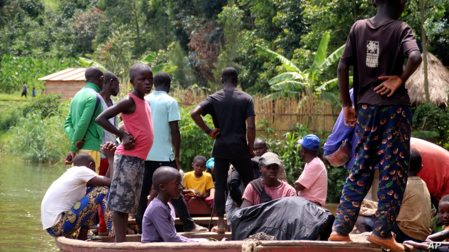 Children gather around a wooden boat conveying two bodies, in Mukwija in Eastern Congo, Wednesday Jan. 6, 2021. Authorities in…