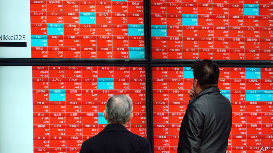 People wearing protective masks watch an electronic stock board showing Japan's Nikkei 225 index at a securities firm Monday,…