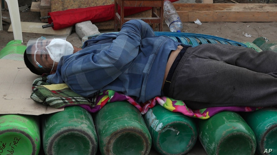 A man sleeps on top of empty oxygen cylinders, waiting for a shop to open to refill his tank, in the Villa El Salvador…
