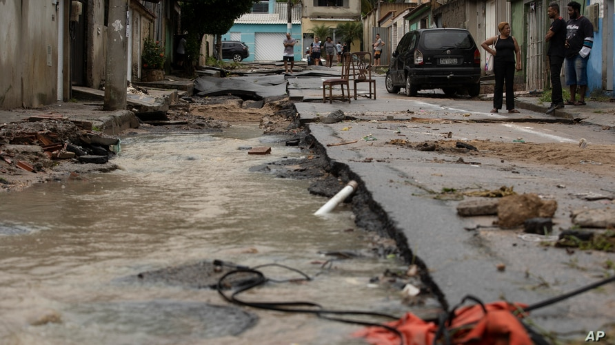 Neighbors look at the damage to a street after heavy rains caused flash floods in the Realengo neighborhood of Rio de Janeiro,…