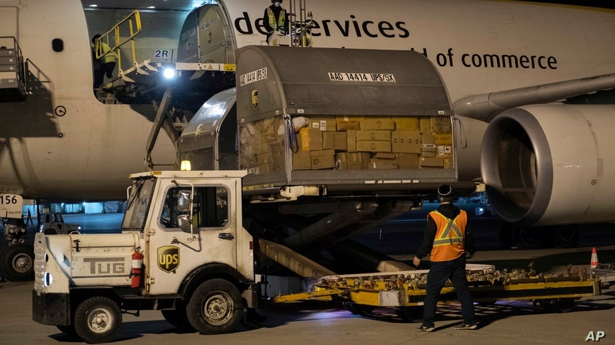 In this photo provided by Canada's Department of National Defence, shipments of initial doses of COVID-19 vaccines are unloaded…