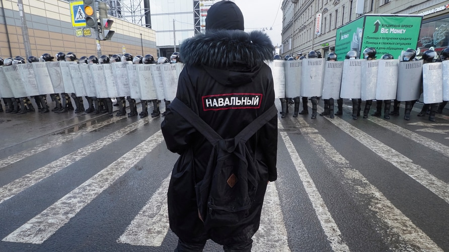 A man with a sign 'Navalny' on his back stands in front of riot policemen blocking the way to protester during a protest…