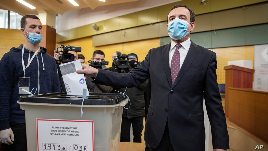 Albin Kurti, right, a candidate for prime minister of Vetevendosje (Self-Determination), casts his ballot paper in…