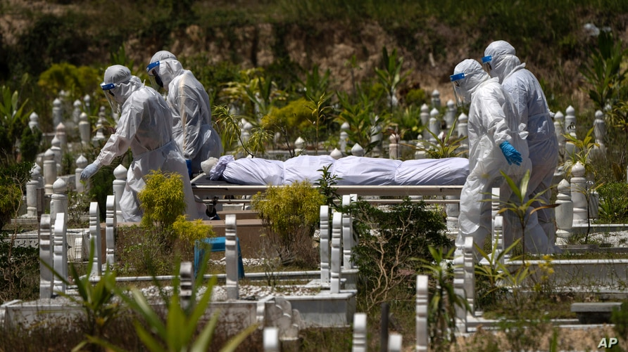 Workers wearing personal protective equipment (PPE) carry the body of a victim of the coronavirus disease at a Muslim cemetery…