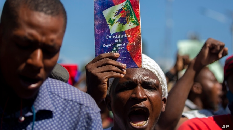 A protester holds up a copy of the Haitian constitution during a protest to demand the resignation of Haiti's president Jovenel…