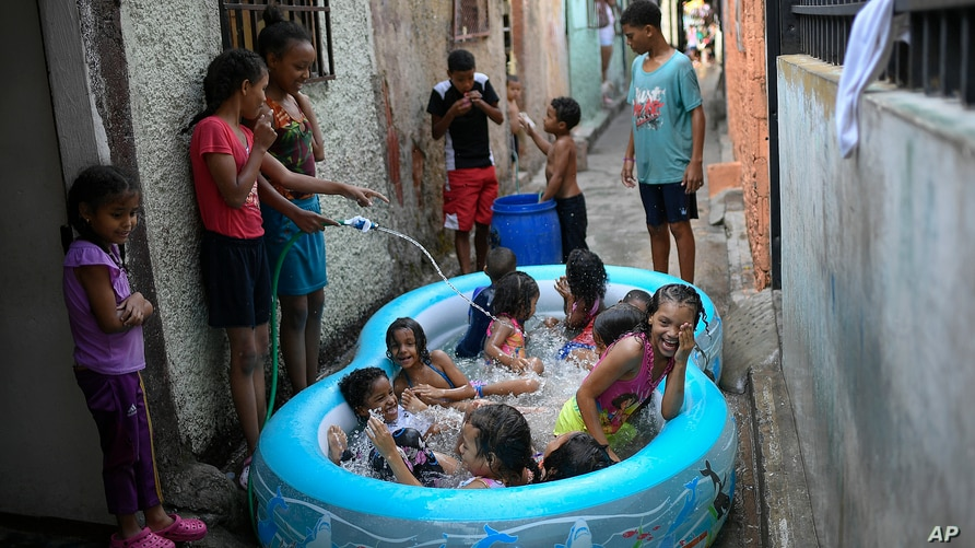 Children play in an inflatable pool during carnival in the Pinto Salinas neighborhood of Caracas, Venezuela, Monday, Feb. 15,…