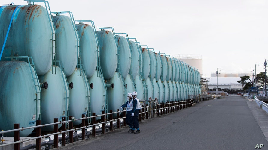 Employees of Tokyo Electric Power Co. look at old tanks which used to store radioactive water at the Fukushima Daiichi nuclear…