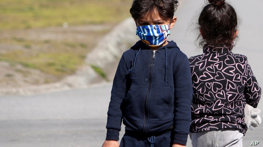 """Migrants children wearing a face mask to protect against coronavirus play in garden during the vaccination in the """"Krnjaca""""…"""