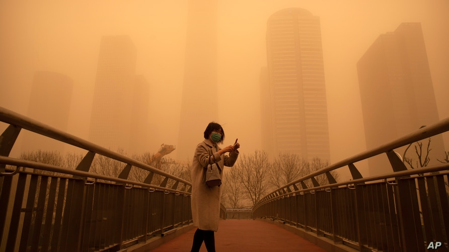 A woman walks along a pedestrian bridge amid a sandstorm during the morning rush hour in the central business district in…