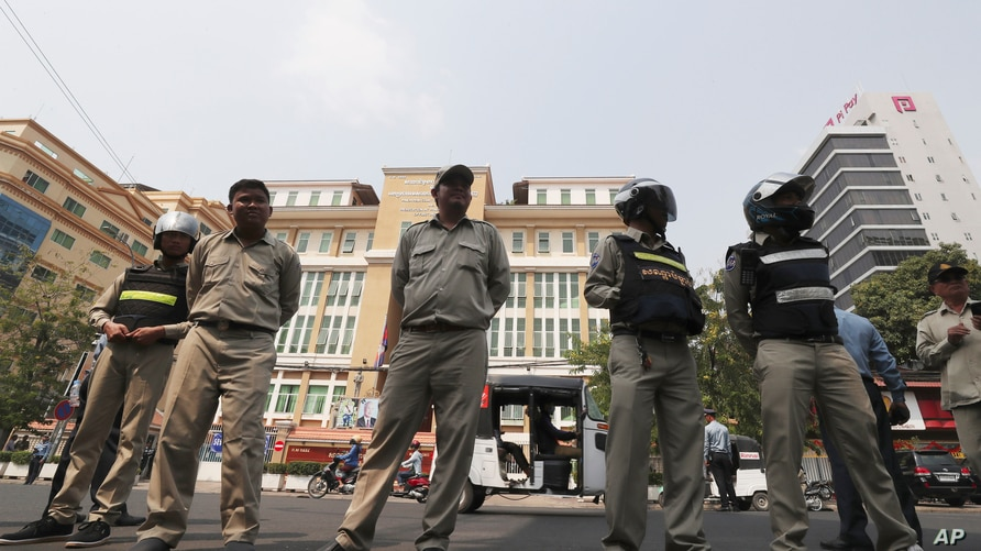 Cambodian police officers stand guard in front of the Phnom Penh Municipal Court during a hearing of Kem Sokha, the head of the…
