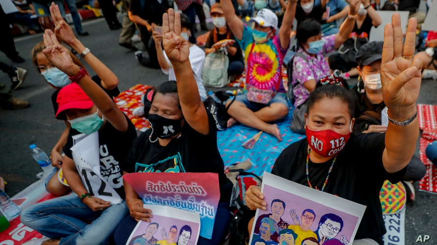 Pro-democracy activists flash a three-fingered symbol of resistance during a rally in Bangkok, Thailand, Wednesday, March 24,…
