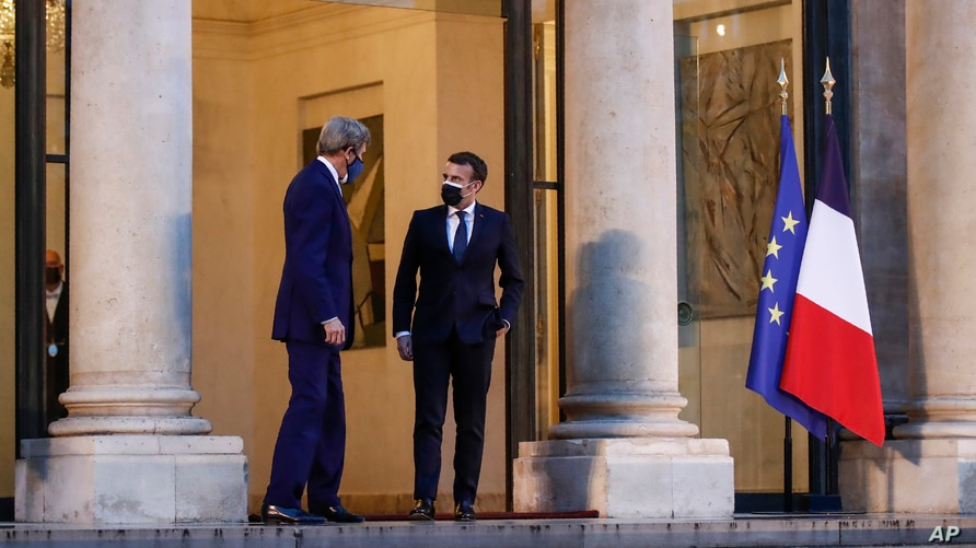 United States Special Presidential Envoy for Climate John Kerry, left, speaks with France's President Emmanuel Macron as he…