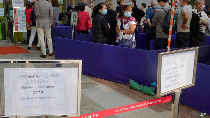 FILE - In this Wednesday, March 24, 2021 file photo, a notice of vaccine suspension, left, is placed as people queue up outside…