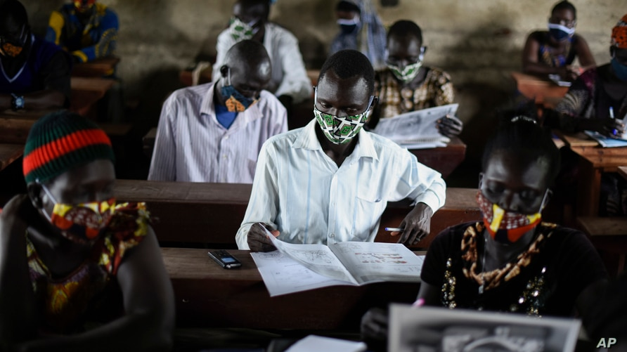 A trainee reads a handbook on coronavirus prevention, at a training session for community health workers conducted by the…