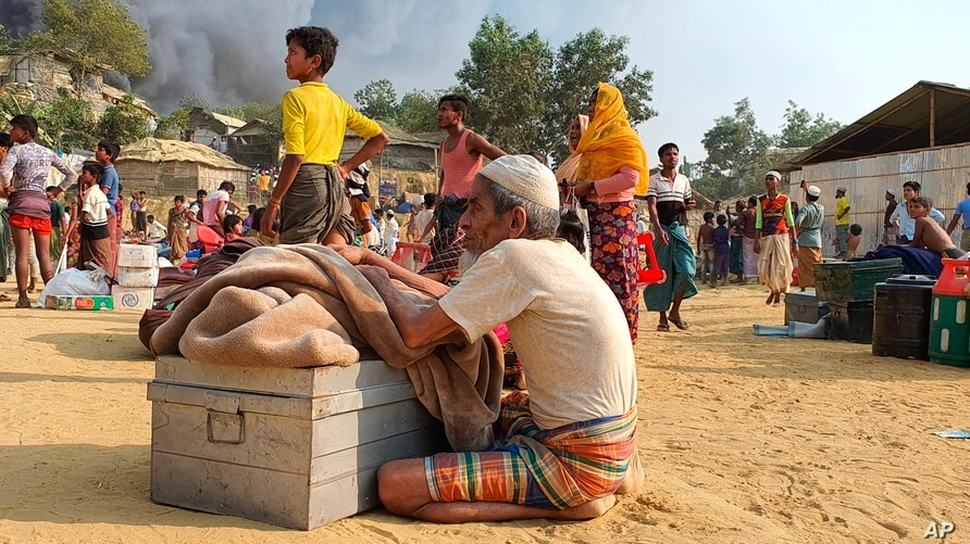Rohingya refugees salvage their belongings and watch smoke rising following a fire at the Rohingya refugee camp in Balukhali,…