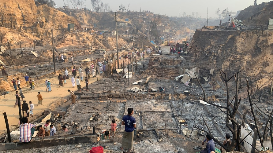 Rohingya refugees look at the remains of Monday's fire at the Rohingya refugee camp in Balukhali, southern Bangladesh, Tuesday,…