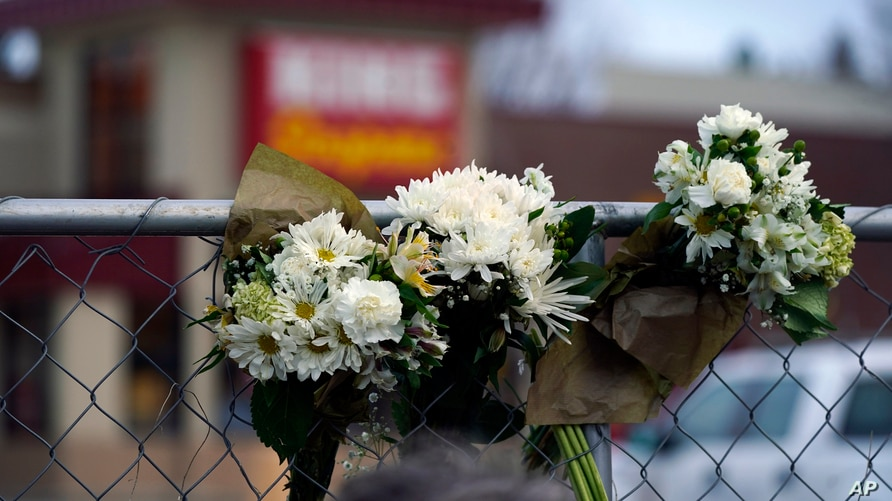 Bouquets line a fence put up around the parking lot where a mass shooting took place the day before in a King Soopers grocery…