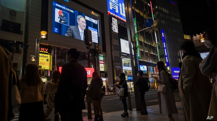Japanese Prime Minister Yoshihide Suga, on a screen, speaks at a news conference in a live broadcasting shown in a big screen…