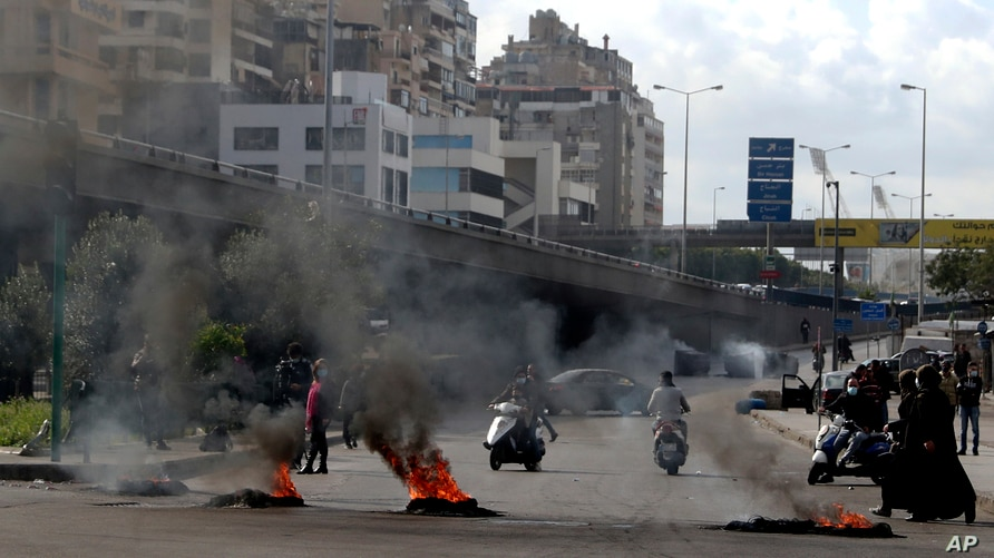Protesters burn tires to block a road in Beirut, Lebanon, Monday, March 8, 2021. The dayslong protests intensified Monday amid…