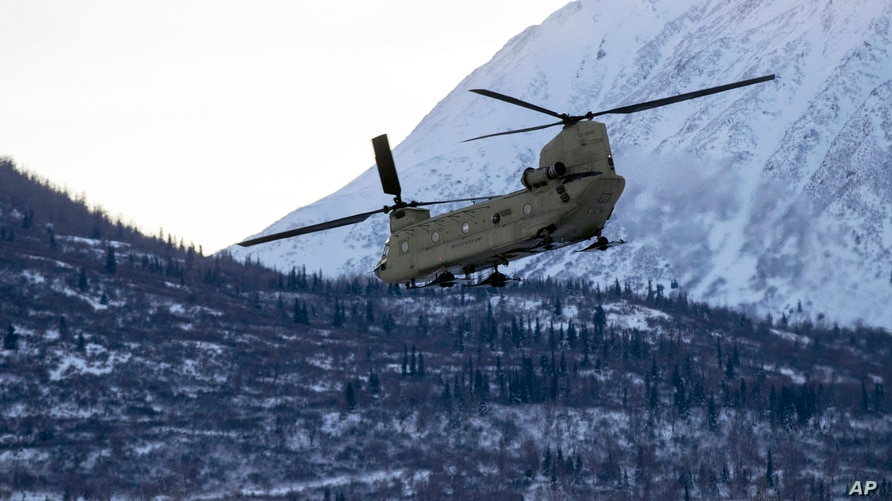 In this photo provided by the Alaska National Guard, a CH-47 Chinook helicopter departs Bryant Army Airfield, Dec. 11, 2020, on…