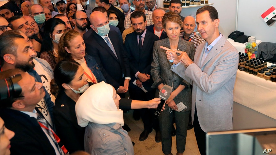 In this photo provided by the official Facebook page of the Syrian Presidency, Syrian President Bashar Assad, right, and first…