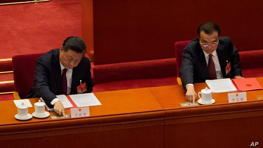 Chinese President Xi Jinping, left, and his Premier Li Keqiang cast their vote during the closing session of the National…