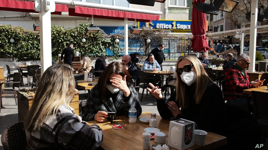 Women chat as they wait to be served at a restaurant reopened for business in Ankara, Turkey, Tuesday, March 2, 2021, as cafes,…