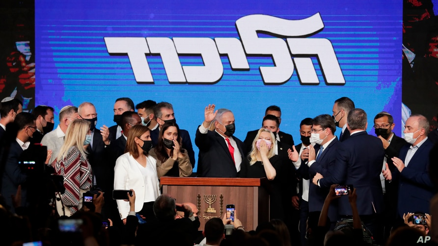 Israeli Prime Minister Benjamin Netanyahu, center, with his party members waves to his supporters after the first exit poll…