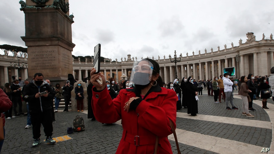 A woman wearing a face mask to curb the spread of COVID-19, uses her phone as Pope Francis recites the Angelus noon prayer from…
