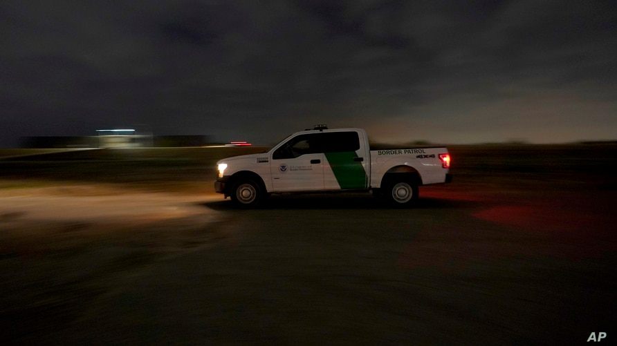 A U.S. Customs and Border Protection truck drives by a road adjacent to the U.S.-Mexico border, late Monday, March 22, 2021, in…