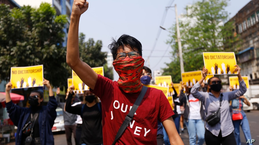 Anti-coup protesters gesture during a march in Yangon, Myanmar, Friday, March 26, 2021. Protesters against last month's…