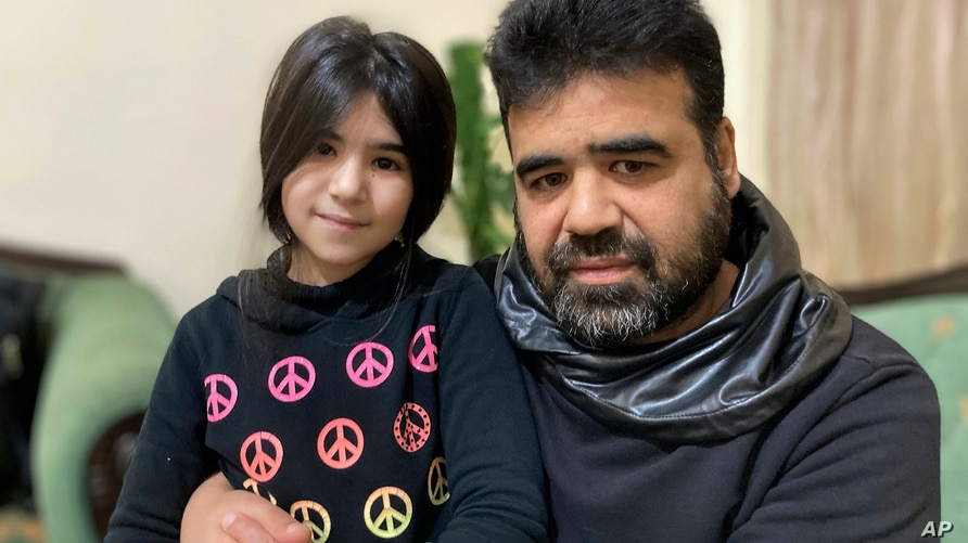 Syrian refugee Mahmoud Mansour, 47, sits with his youngest daughter Sahar, 8, at his rented apartment in Amman, Jordan,…