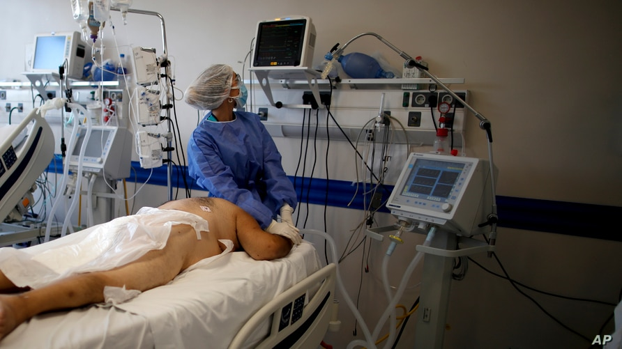 A healthcare worker tends to a COVID-19 patient at the Dr. Norberto Raul Piacentini hospital, in Lomas de Zamora, Argentina,…