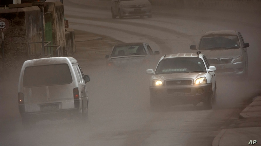 Vehicles drive on the main Black Rock road, covered with ash coming from the St. Vincent eruption of La Soufriere volcano, on…