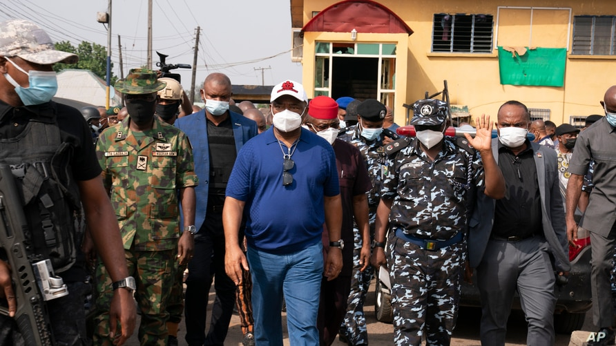 Imo state Gov. Hope Uzodinma, center, inspects the scene of an attack at the police command headquarters in Owerri, Nigeria, on…