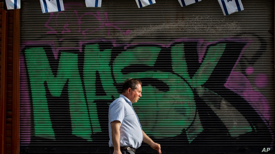 """A man without a face mask walks by a """"mask"""" graffiti in downtown Tel Aviv, Israel"""